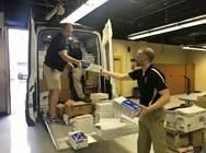 Two men load a van of supplies