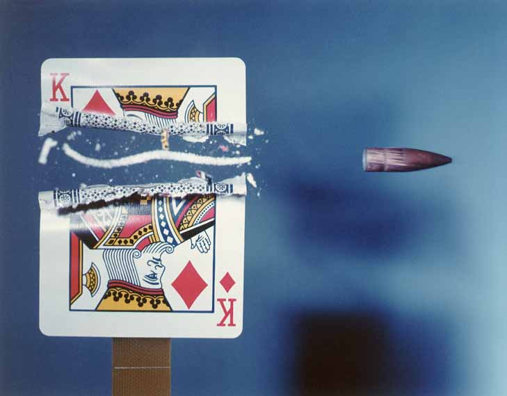 Playing card cut in half by bullet